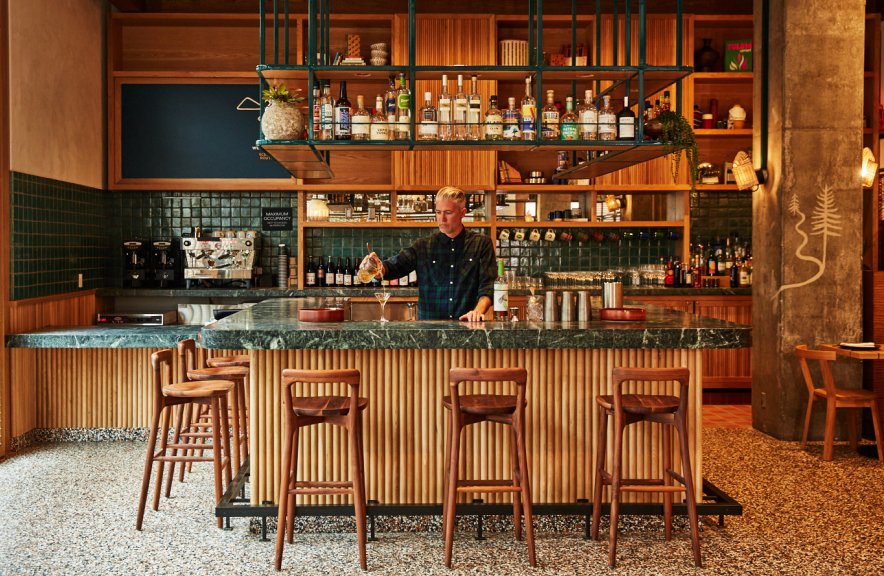 Bartender pouring drink from behind bar, stools in the foreground
