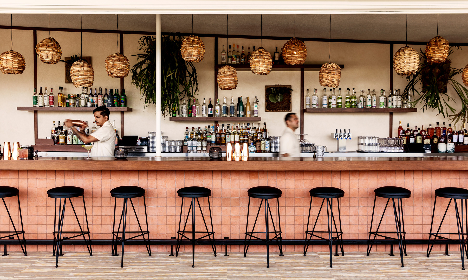Long bar with stools and bartenders working in front of various liquor bottles